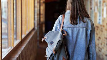 Een foto van een buitenlandse student die door een gang van een school loopt.