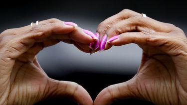 Een foto van twee donkere handen die bij een demonstratie in Utrecht een hartje vormen