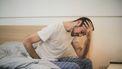 man zit op rand van bed en kan niet slapen zonder stress te verminderen