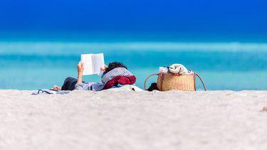 man heeft vakantiedagen opgenomen en ligt op het strand