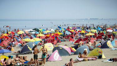 Op deze foto is het strand van Scheveningen te zien, met daarop veel badgasten. Het is druk, veel mensen gebruiken een parasol.
