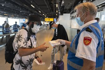 Een foto van een vliegtuigpassagier die door de GGD gecontroleerd wordt op Schiphol