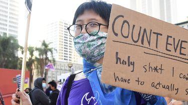 Een vrouw houdt een bord vast met 'count every vote'.