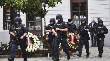 Een foto van agenten in Wenen die hun eer betuigen aan de slachtoffers