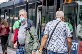 Op deze foto zie je een man in Rotterdam uit de metro stappen die een mondkapje draagt