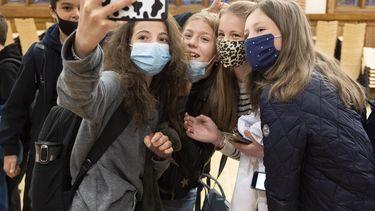 Op deze foto zijn scholieren te zien met mondkapjes op. Ze maken een selfie.