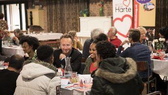 Op deze foto is Joris Linssen te zien, hij zit met een groepje mensen aan tafel in een restaurant van Resto VanHarte