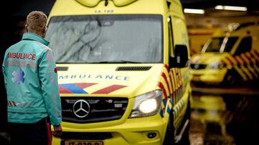 Op deze foto is een ambulancebroeder te zien die op een ambulancebus afloopt.