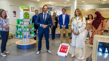 Een foto van Olcay Gulsen en minister Hugo de Jonge bij de introductie van het codewoord 'masker 19'.