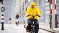 Een foto van een man die door een stortbui fietst.