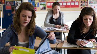 Op deze foto zie je scholieren met schoolboeken op school. Jongeren voelen zich ongehoord over de corona-aanpak.
