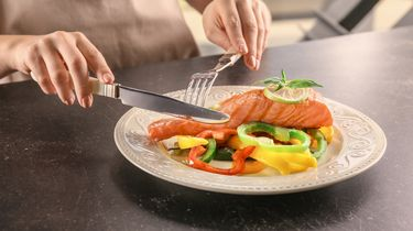 Een foto van een bord met zalmfilet gegarneerd met paprika erop. Iemand buiten beeld staat op het punt met mes en vork te gaan eten.
