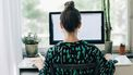 Een foto van een vrouw, thuiswerkend achter haar computer