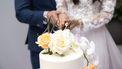 Bruid en bruidegom snijden taart aan.
