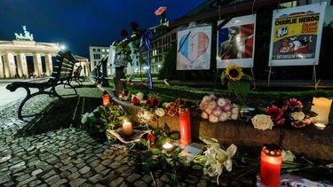 Op deze foto is de gedenkplek voor de leraar te zien, met kaarsen en bloemen.