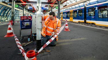Een foto van een man die een rookpaal verwijdert om station Sloterdijk rookvrij te maken