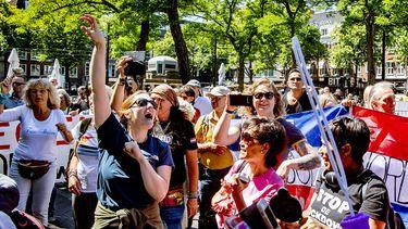 Op deze foto zie je demonstranten protesteren tijdens een mars door Den Haag tegen de coronaregels.