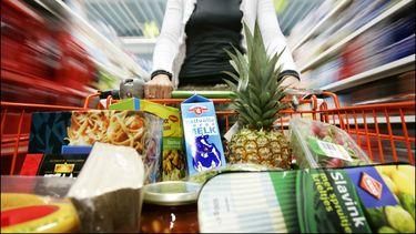 Een foto van een supermarktwagentje vol producten