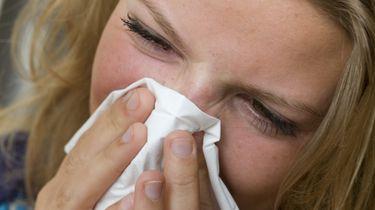 Een foto van een niezende vrouw met een zakdoek