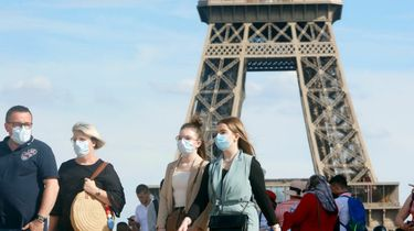 Een foto van mensen met mondkapjes bij de Eiffeltoren in Parijs