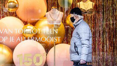 Een foto van een man met een mondkapje in een winkelstraat in Den Haag