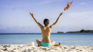 Een foto van een topless dame op het strand, op de rug gezien