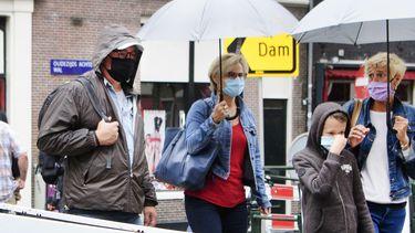 Een foto van toeristen, zaterdag in Amsterdam met paraplu's