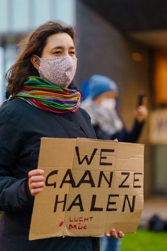Een foto van een actievoerster met een bordje met de tekst We Gaan Ze Halen