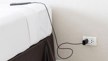 Tiener laat telefoon op bed laden, kamer brandt af