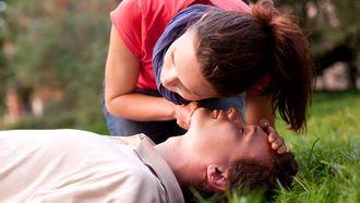 Op deze foto zie iemand die mond-op-mond beademing krijgt.