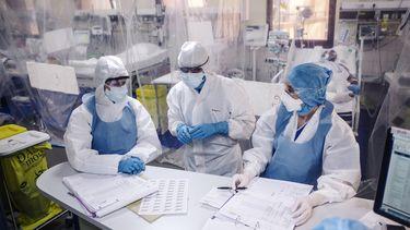 Op deze foto zijn drie artsen in het ziekenhuis te zien. Ze dragen beschermde kleding.