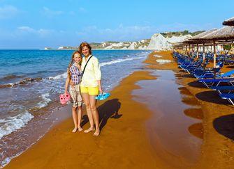 Een moeder en dochter maken een strandwandeling op Xi beach. / Colourbox