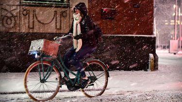 Een fietser op een besneeuwde straat.