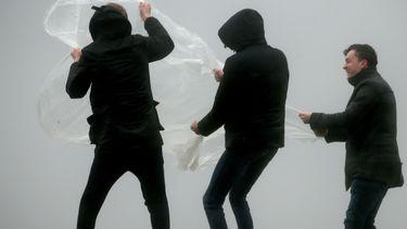 Een foto van drie jongens op een dijk in een storm