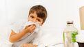 Een foto van een jongetje met een snotneus en een zakdoek