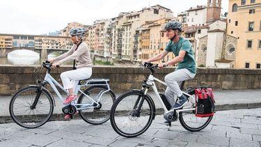 Een foto van twee fietsers op een brug