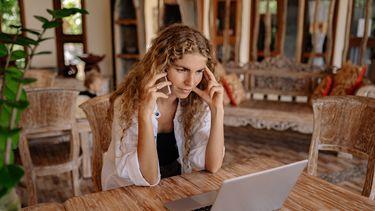 vrouw telefoneert en beantwoordt mail gedurende werkdag