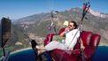 Een paraglider die op zijn bankstel en met televisie de berg af paraglide.