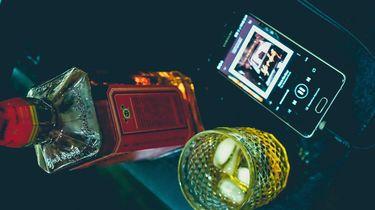 Foto van een fles whiskey een glas en een mobiele telefoon