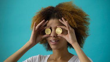 Een foto van een vrouw die bitcoin voor haar ogen houdt