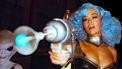 Een foto van Rita Ora met blauw haar een een scifi-wapen, links van haar staat een alien
