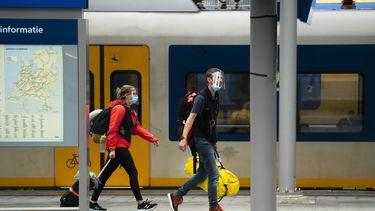 Een foto van twee reizigers op het perron van een treinstation