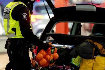 Een douanier haalt een zak sinaasappels uit een auto.