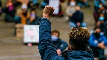 Op deze foto zie je anti discriminatie demontranten die elkaar helpen. 'Landelijk coördinator nodig om discriminatie aan te pakken'.