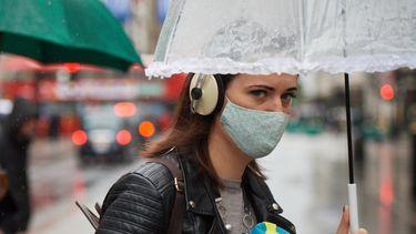 Een foto van een vrouw met een paraplu in de regen