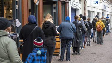 Een foto van een lange rij voor een winkel in Amsterdam, kort voor de lockdown