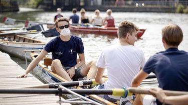 Op deze foto zijn studenten in een roeiboot te zien, een van hen draagt een mondmasker.