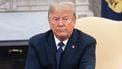 Een foto van Donald Trump, sip kijkend met zijn armen over elkaar