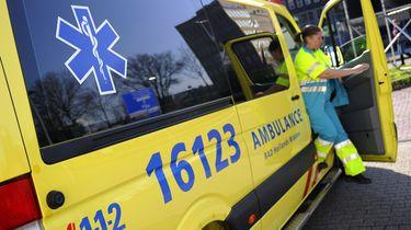 Een medewerker stapt uit een ambulance.