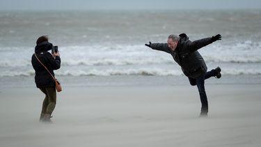 Een man op het strand die op 1 been in de storm hangt